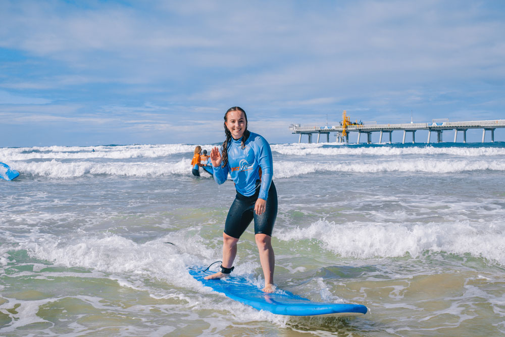 Lady waving while on a surfing lesson with Get Wet Surf School