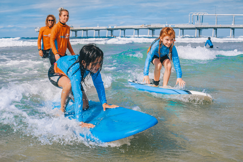 Two kids surfing with two surfing instructors watching