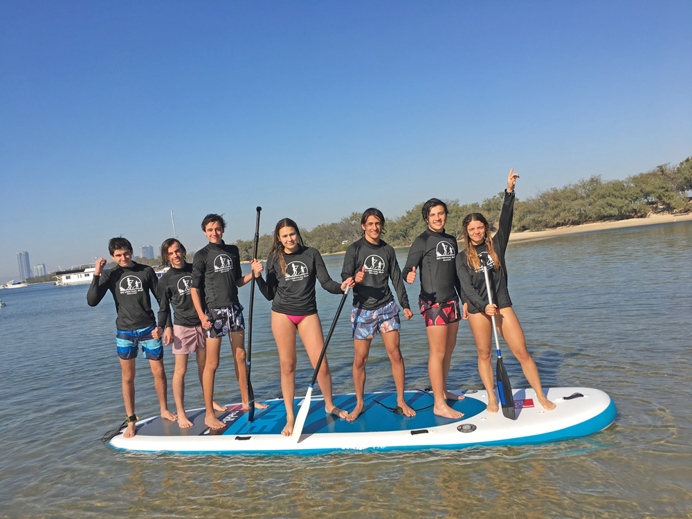 Seven teenagers having fun on a large SUP