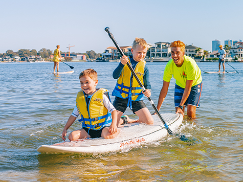 Kids on a stand up paddle board in Surfers Paradise